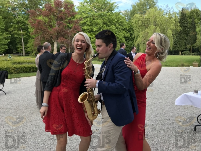 Saxophonist mit Hochzeitsgästen vor Schloss Gartrop