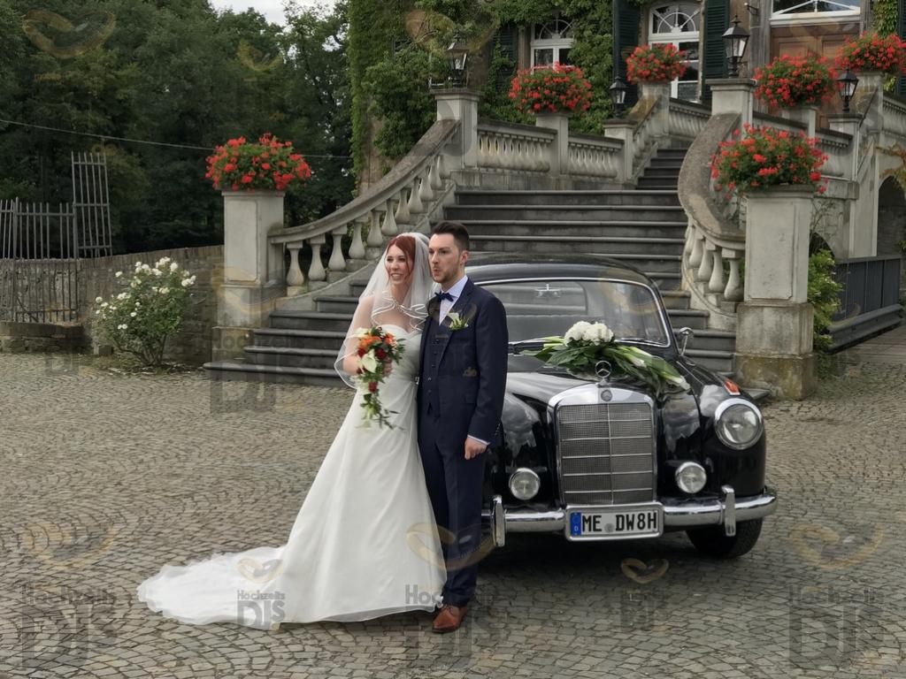 Brautpaar mit Oldtimer vor Schloss Linnep