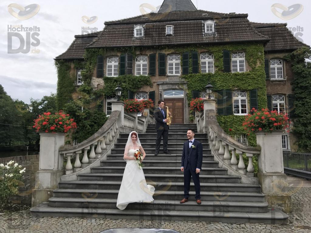 Brautpaar mit Saxophonist vor Schloss Linnep